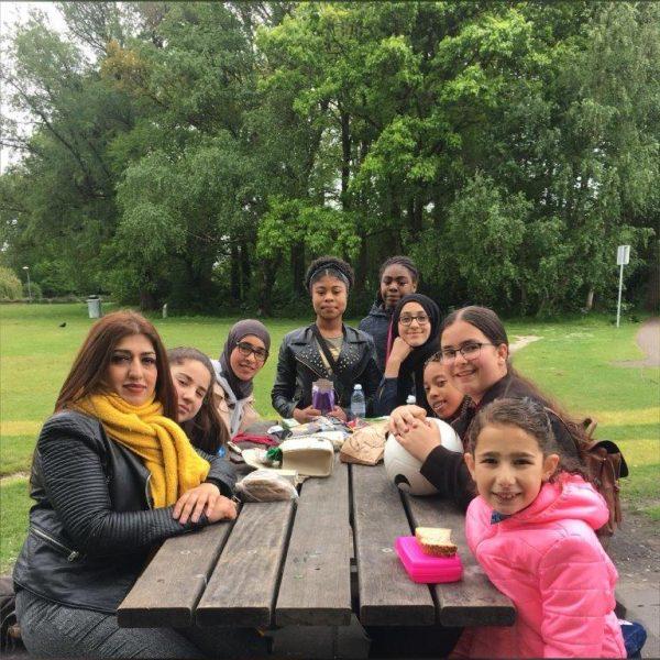 Meiden en juf Moska op bank in Zuiderpark