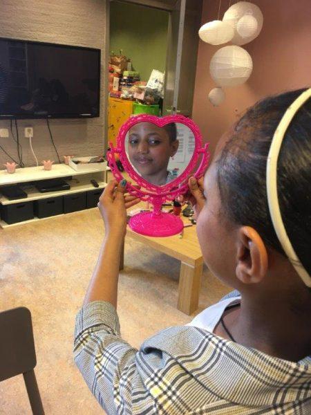 Meisje ziet zichzelf in spiegel