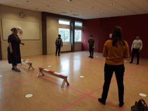 Kinderen staan in een zaal en zijn bezig met sport
