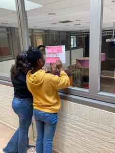 2 kinderen staan voor een raam en schrijven iets op een vel papier