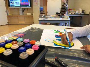 Kind maakt een tekening met verschillende kleuren verf